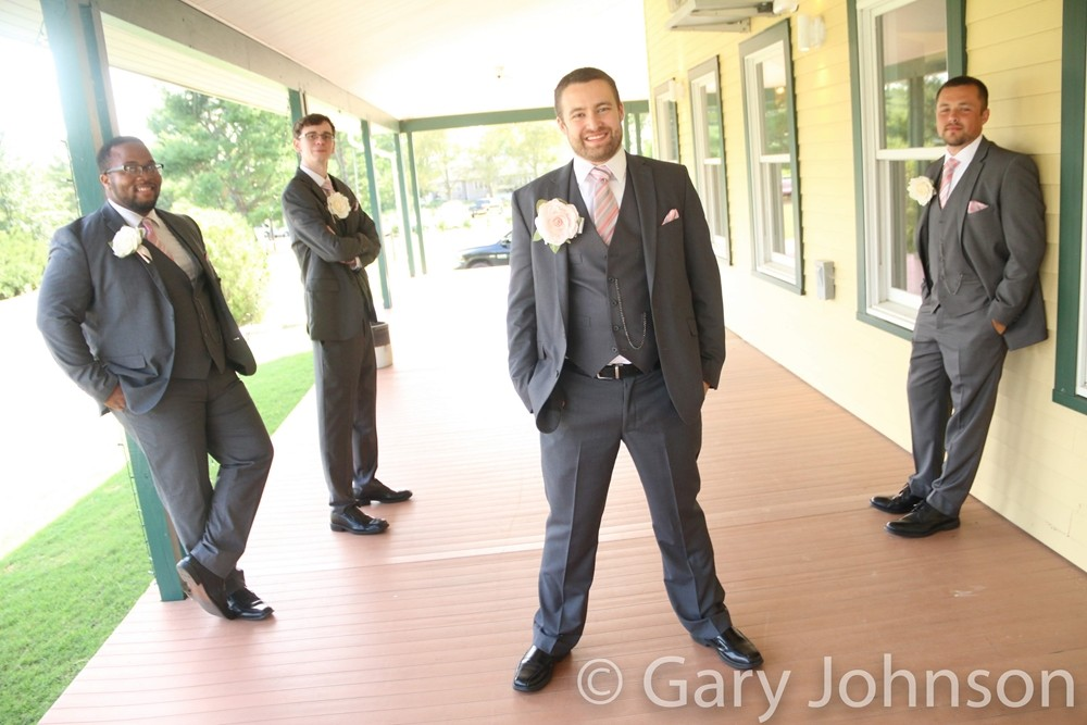 Four men in grey tuxes spread out posing for photo