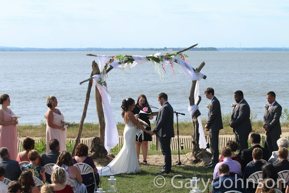 Wedding on beach with bride and groom under manor