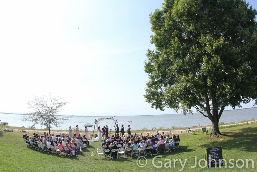 Ongoing outdoor wedding next to ocean and large tree