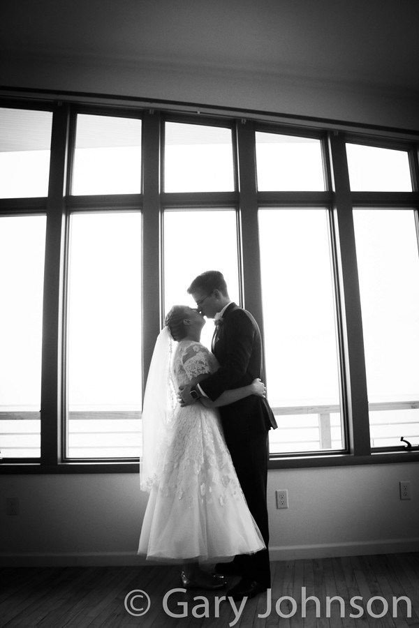 Black and white photo of bride and groom kissing infront of windows