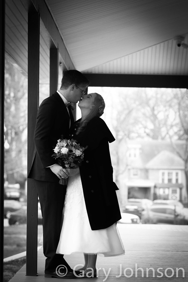 Black and white photo of bride and groom kissing outside
