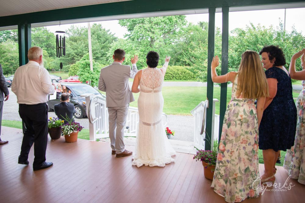 Newlyweds waving from front porch