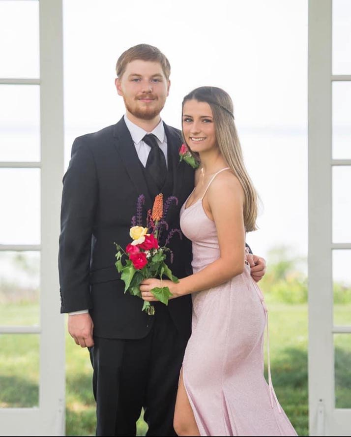 High school age prom couple standing