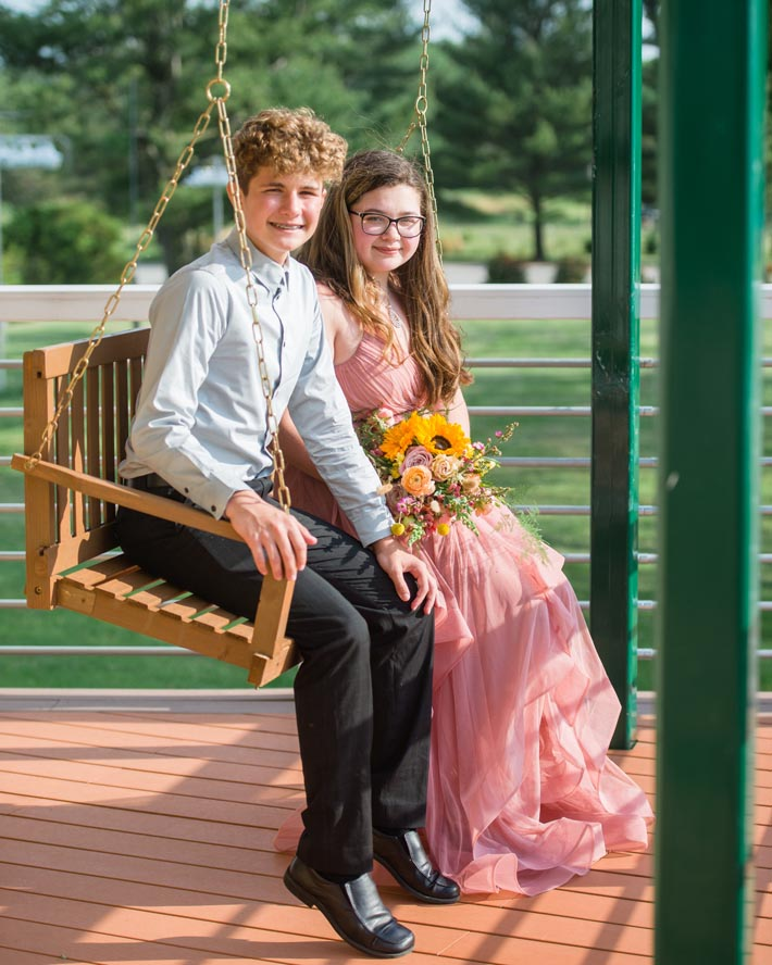 Prom boy and girl sitting on porch swing