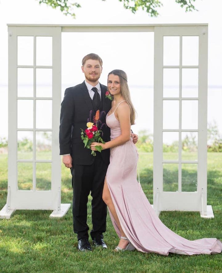 Newly wed couple standing outside in front of windowed backdrop