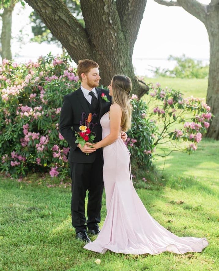 Bride and groom with spring flowering bush behind them