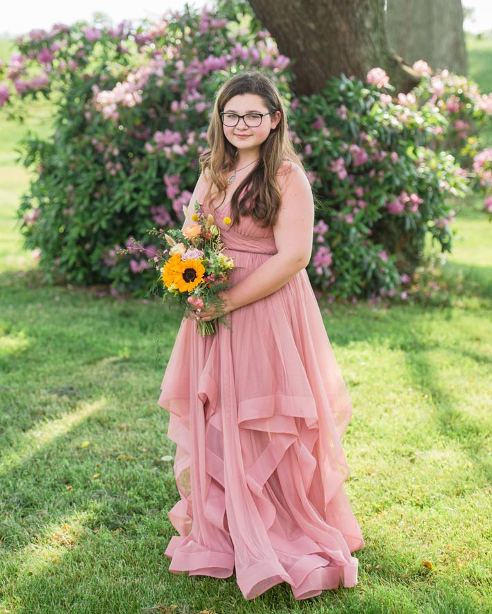 Young lady in coral gown hlding bouquet
