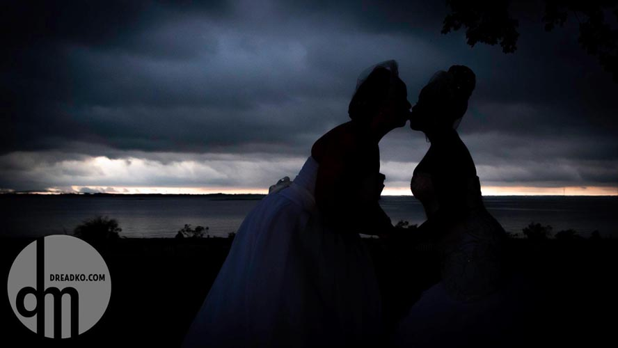 Silhouette of kissing brides