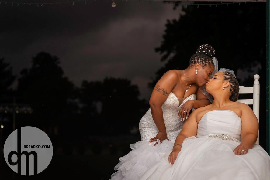 Two brides kissing sitting outdoors at night