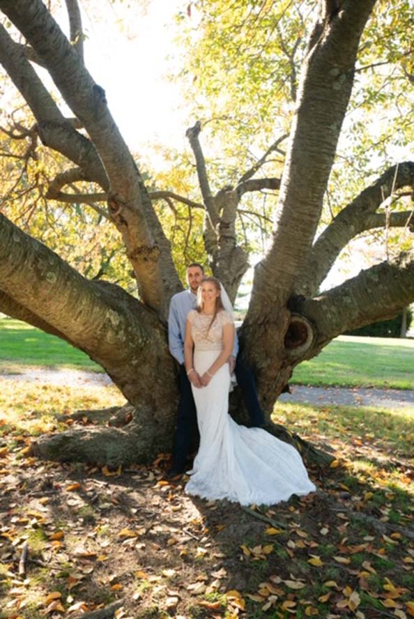 Bride and groom infront of large tree