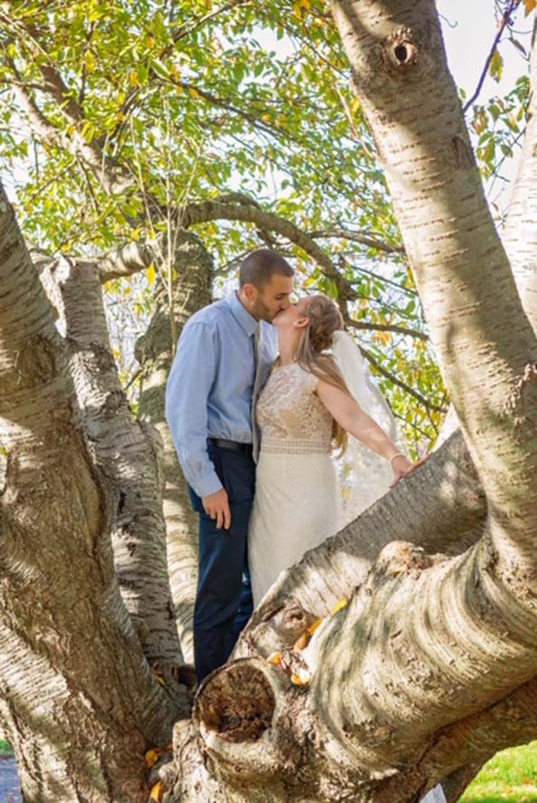 Bride and groom kissing infront of tree