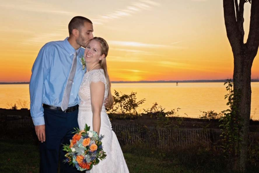 Groom kissing bride's forehead infront of sunset