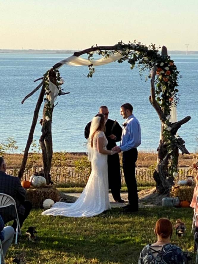 Bride and groom getting married under arch