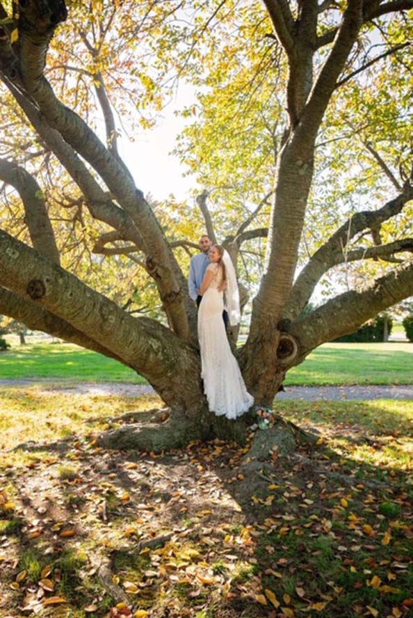 Bride and groom standing infront of large tree