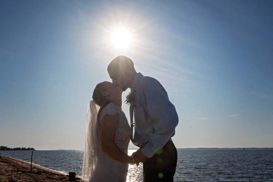 Bride and groom kissing infront of sun