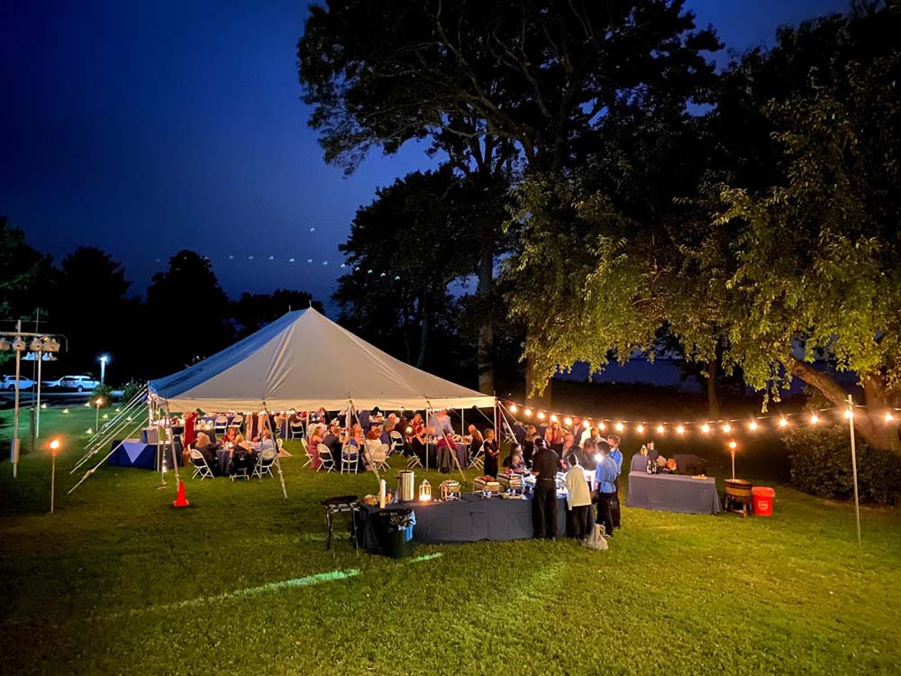 Large event tent outdoors with people sitting under